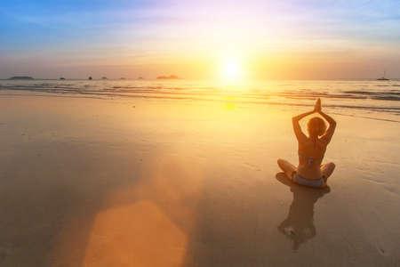 Silhouette of Yoga woman doing meditation near the ocean beach. photo