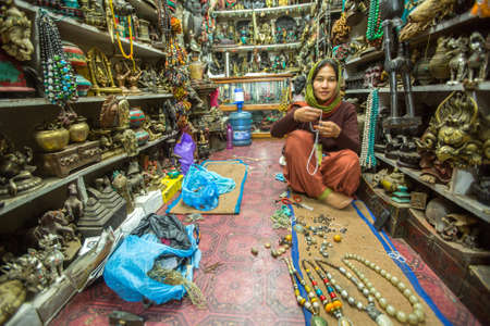capita: BHAKTAPUR, NEPAL - CIRCA DEC 2013: Unidentified woman seller in the Studio souvenirs in shop at Durbar Square. More 100 cultural groups have created an image of Bhaktapur as Capital of Nepal Arts.