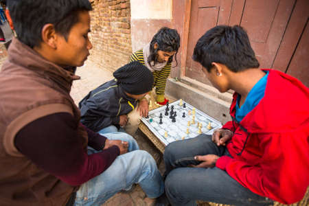 rigid: BHAKTAPUR, NEPAL - CIRCA DEC 2013: Unidentified local people playing chess in the street. The caste system is still intact today but the rules are not as rigid as they were in the past. Editorial