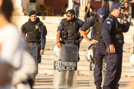 austerity: ATHENS, GREECE - APR 16, 2015: Riot police with their shield, take cover during a rally in front of the Athens University, which is under occupation by protesters leftist and anarchist groups.