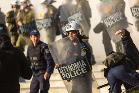 protesters: ATHENS, GREECE - APR 16, 2015: Riot police with their shield, take cover during a rally in front of the Athens University, which is under occupation by protesters leftist and anarchist groups.
