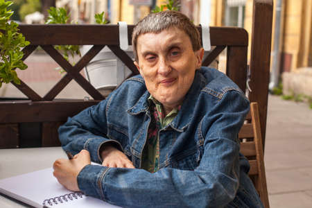 cerebral palsy: Elderly disabled man with cerebral palsy writing in notebook. Stock Photo