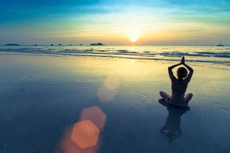 composure: Silhouette of yoga woman meditating on the ocean beach.