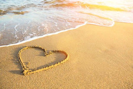 Heart drawn on the sand of a sea beach, soft wave and solar glare.