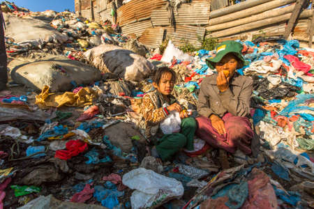 dumps: KATHMANDU, NEPAL - CIRCA DEC, 2013: Unidentified child and his parents during lunch in break between working on dump. Only 35% of population Nepal have access to adequate sanitation. Editorial