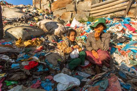 niños reciclando: KATMANDÚ, NEPAL - CIRCA diciembre de 2013: el niño no identificado y sus padres durante el almuerzo en ruptura entre trabajar en vertedero. Sólo el 35% de la población de Nepal tienen acceso a un saneamiento adecuado.