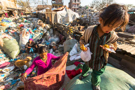 KATHMANDU, NEPAL - CIRCA DEC, 2013: Unidentified child and his parents during lunch in break between working on dump. Only 35% of population Nepal have access to adequate sanitation. Éditoriale
