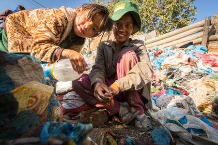 sanitation: KATHMANDU, NEPAL - CIRCA DEC, 2013: Unidentified child and his parents during lunch in break between working on dump. Only 35% of population Nepal have access to adequate sanitation. Editorial