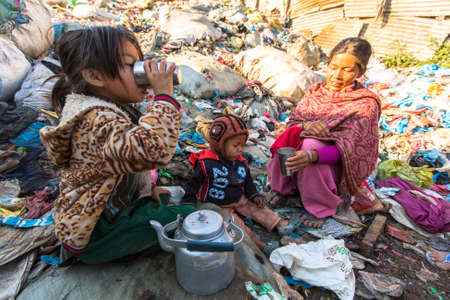 adequate: KATHMANDU, NEPAL - CIRCA DEC, 2013: Unidentified child and his parents during lunch in break between working on dump. Only 35% of population Nepal have access to adequate sanitation. Editorial