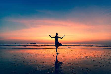 Yoga silhouette. Woman doing meditation near the ocean. photo