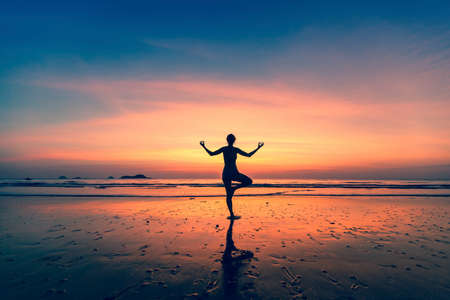 yoga sunset: Yoga silhouette. Woman doing meditation near the ocean.