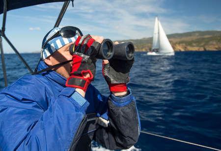 Griekse schipper kijkt door een verrekijker op zijn jacht.