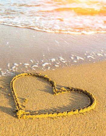 dia soleado: Corazón dibujado en la arena de la playa del mar, onda suave en un día soleado. Foto de archivo
