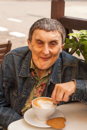 cerebral palsy: Elderly disabled man with cerebral palsy sitting at outdoor cafe with cup of coffee.