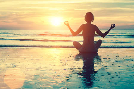Female silhouette in yoga meditation pose at amazing sunset on the sea.
