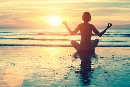 Weibliche Silhouette in Yoga Meditation Pose zu erstaunlichen Sonnenuntergang am Meer.