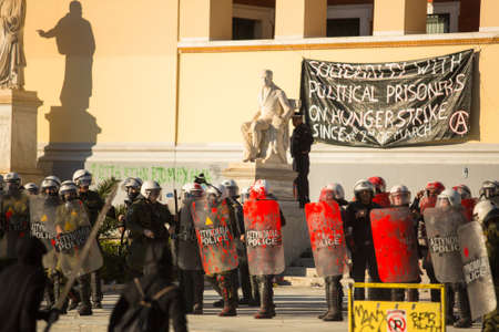 anarchist: ATHENS, GREECE - CIRCA APR, 2015: Riot police with their shield, take cover during a rally in front of Athens University, which is under occupation by protesters leftist and anarchist groups. Editorial