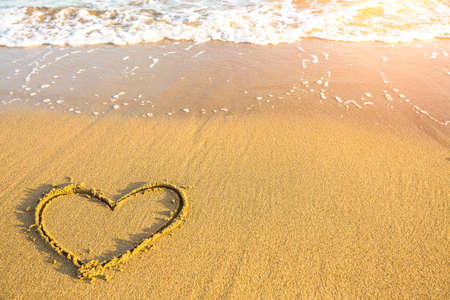evoking: Heart drawn on the sand of ocean beach.
