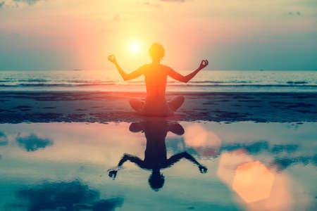 Meditation Silhouette Mädchen auf dem Hintergrund der atemberaubenden Meer und den Sonnenuntergang. Yoga, Fitness und gesunde Lebensweise.
