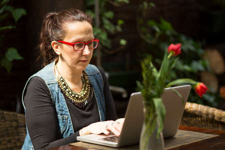 Female freelancer with a laptop in a summer cafe. photo