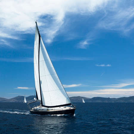 is cloudless: Sailing. Yacht sails with beautiful cloudless sky. Luxury yacht.