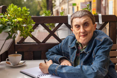 cerebral palsy: Elderly disabled man with cerebral palsy in outdoor cafe. Stock Photo