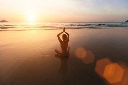 Beautiful girl sitting on the beach during sunset and meditating in yoga pose. Standard-Bild