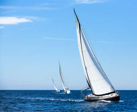 Sailing in the wind through the waves at the Aegean Sea in Greece. Luxury yachts.