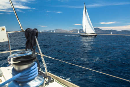 sailboat race: Sailboats competitor of sailing regatta in clear sunny weather. Luxury yachts on Mediterranean sea.