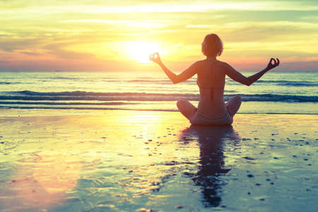 pose: Silhouette of woman at yoga pose on the beach during an amazing sunset. Stock Photo