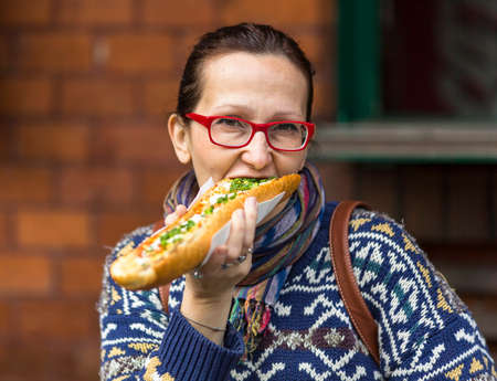 krakow sausage: Young woman eating Polish fast-food – casserole (Zapiekanka)
