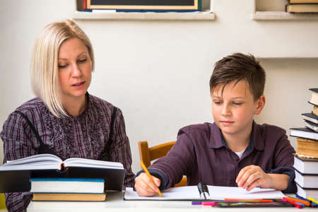 Young student learns at home with a his mom tutor. Stockfoto