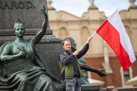 bandera de polonia: Hombre joven con la bandera polaca cerca de monumento Mickiewicz en la plaza principal de Cracovia, Polonia. Foto de archivo