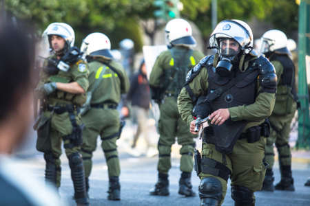 clashes: ATHENS, GREECE - CIRCA APR, 2015: Riot police with their shield, take cover during a rally in front of Athens University, which is under occupation by protesters leftist and anarchist groups. Editorial