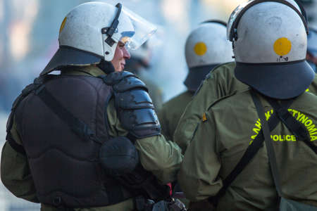 protesters: ATHENS, GREECE - CIRCA APR, 2015: Riot police with their shield, take cover during a rally in front of Athens University, which is under occupation by protesters leftist and anarchist groups. Editorial