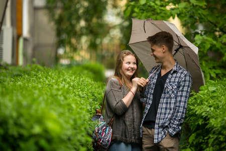 sotto la pioggia: Coppia giovane ragazzo e ragazza all'aperto sotto un ombrello nella piccola pioggia. Archivio Fotografico