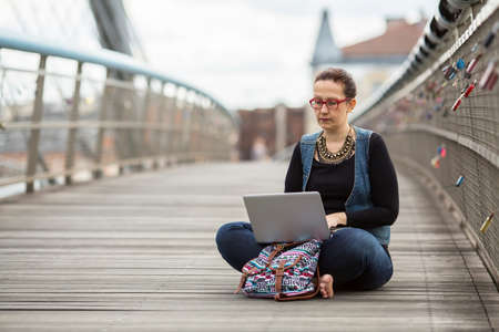 freelancing: Young woman uses a laptop sitting outdoors. Conceptual photo about freelancing. Stock Photo