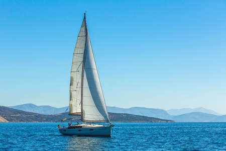 sailboat race: Yacht is moving along the coast. Sailing yacht in blue sea.