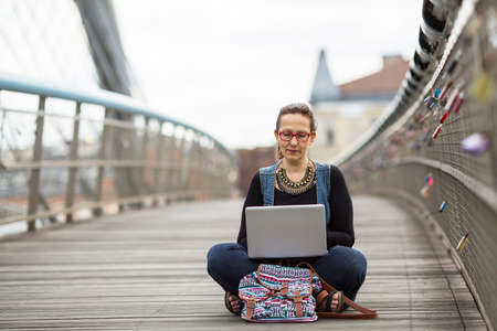 freelancer: Young woman with laptop sitting on a pedestrian bridge. Freelancer.