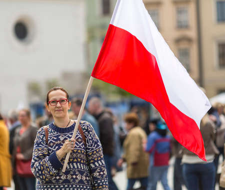 Polonia: Young woman on the street with the flag of Republic of Poland.