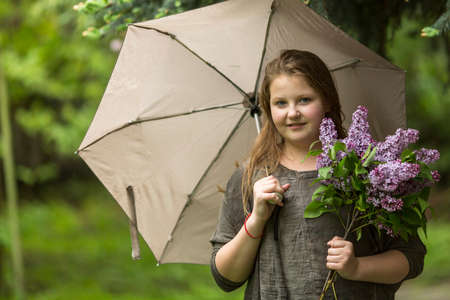 lilacs: Portrait of teen girl with an umbrella and a bouquet of lilacs. Stock Photo