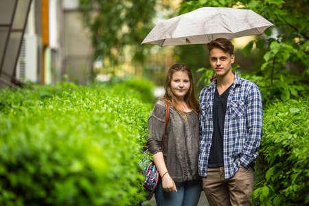 sotto la pioggia: Coppia giovane, ragazzo e ragazza in piedi sotto un ombrello sulla pista verde nel cortile davanti vicino alla casa, guardando la telecamera.