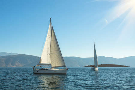 yacht: Sailing. Luxury yachts in the sea near the Greek Islands in the rays of the rising sun.
