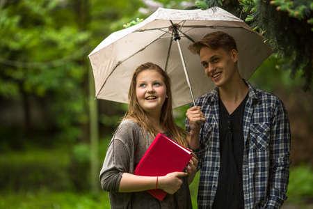 sotto la pioggia: Giovane coppia in parco sotto un ombrello, una ragazza tiene un libro rosso nelle sue mani.