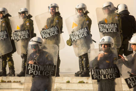 ATHENS, GREECE - CIRCA APR, 2015: Riot police with their shield, take cover during a rally in front of Athens University, which is under occupation by protesters leftist and anarchist groups. Editorial