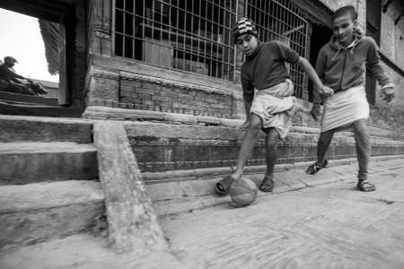 sanskrit: KATHMANDU, NEPAL - CIRCA DEC, 2013: Unknown children play football after lesson at Jagadguru School. School established at 2013, to let new generation learn Sanskrit and preserve Hindu culture.