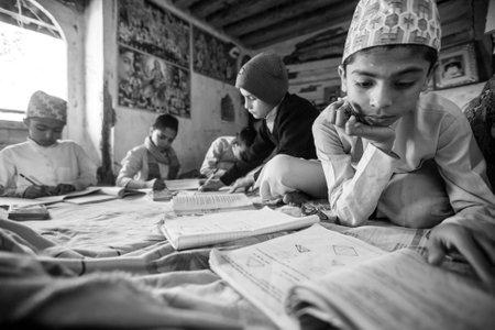 sanskrit: KATHMANDU, NEPAL - CIRCA DEC, 2013: Unknown children doing homework at Jagadguru School. School established at 2013, to let new generation learn Sanskrit and preserve Hindu culture.