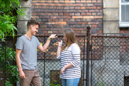 other side of: Teenagers, boy and girl talking on the street. Stock Photo
