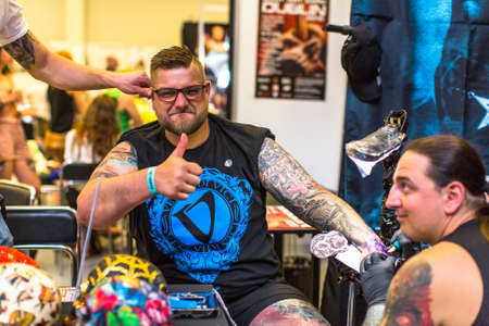 tattoo: KRAKOW, POLAND - JUNE 6, 2015: People make a tattoos at the 10-th International Tattoo Convention in the Congress-EXPO Center. This year anniversary TattooFest is tattoo Studio with an area of 2000m2. Editorial