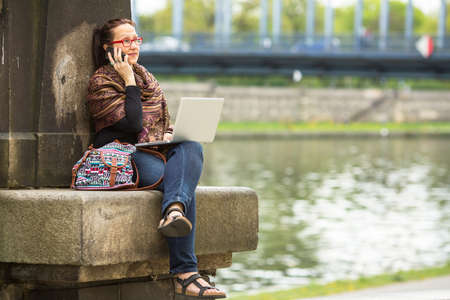 Young woman sitting with laptop outdoors in the city and talking on the phone. photo